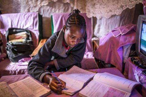 Sheila Achieng doing her studies at home in Kibera.
