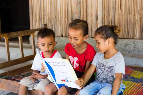 A girl reads as children look on in Timor-Leste