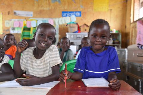 Young children have a light moment during a classroom session at a UNICEF-supported child friendly space in Adjumani District.