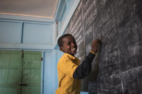 A student laughs as he writes the answers to questions on the chalkboard of his classroom.
