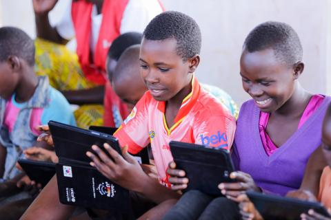 Burundian refugee children in one of Mahama Camp's child-friendly spaces play with educational apps