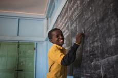 A student laughs as he writes the answers to questions on the chalkboard of his classroom in his UNICEF-supported primary school, Salaama in Galkayo, Somalia, Wednesday, April 12, 2017.