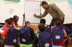 Syrian child refugees learn to count in English in a makeshift tent classroom
