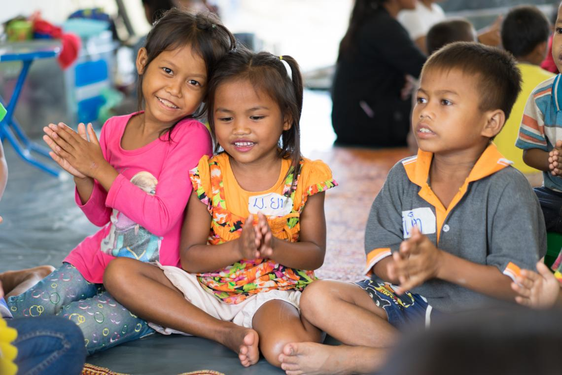 Two girls smile and enjoy a singing activity in a UNICEF-supported Child Friendly Space in Ban Bok camp, Attapeu, Lao PDR.
